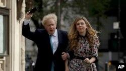 El primer ministro británico, Boris Johnson, llega a un colegio electoral con su cónyuge Carrie Symonds para emitir su voto en las elecciones del consejo local, en Londres , el 6 de mayo de 2021.