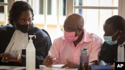 """Paul Rusesabagina, au centre, dont l'histoire a inspiré le film """"Hotel Rwanda"""", porte un uniforme de prison rose alors qu'il comparaît devant un tribunal de la capitale Kigali, Rwanda, le 25 septembre 2020."""