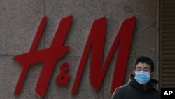 A man wearing a face mask walks by a Swedish fashion brand H&M store outlet in Beijing, March 25, 2021.