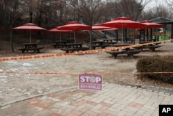 """FILE - A part of park is taped off with a sign which reads """"Access restrictions to prevent the spread of COVID-19"""" for the social distancing measures and a precaution against the coronavirus at a park in Seoul, Dec. 23, 2020."""