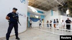 Polisi akishika zamu wakati watu wapiga kura katika duru ya pili ya uchaguzi warais Tunisia, mjini Tunis, Tunisia, Oct. 13, 2019.