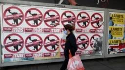 "Seorang pejalan kali melewati poster yang bertuliskan ""Jangan Bayarkan Utang. Keluar dari IMF"" yang terpasang di jalanan kota Buenos Aires, Argentina, pada 27 Mei 2020. (Foto: Reuters/Agustin Marcarian)"