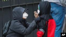 Žena namješta djetetu zaštitnu masku dok čekaju da budu testirani na Covid-19 u New Yorku, 23. aprila 2020.