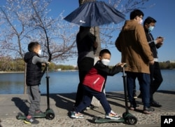 Visitors wear masks at a park during a sunny day in Beijing, March 19, 2020. China has only just begun loosening draconian travel restrictions within the country amid the coronavirus outbreak.