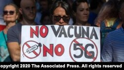 FILE - Demonstrators attend a protest against nationwide restrictions against COVID-19 in Madrid, Spain, Aug. 16, 2020. A banner reads in Spanish 'No vaccine No 5G No mask'.