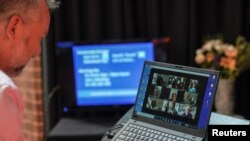 Pastor Matt Johnson interacts with parishioners via Zoom on a laptop upon concluding an Easter service he led which is live-streamed via the internet for the parishioners due to social gathering restrictions implemented to curb the spread of the…