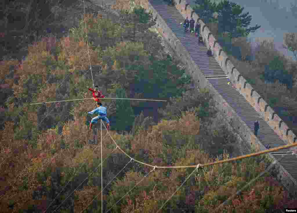"Adili Wuxor (back, in red), who is known as ""Prince of the Tightrope"", and his apprentice balance on a tightrope above the Great Wall in Tianjin, China."