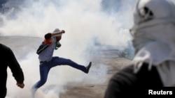 在西岸冲突中,一名巴勒斯坦抗议者踢走以色列军队投掷的催泪弹。(2015年10月29日)