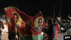 Supporters of Zambian opposition presidential candidate Hakainde Hichilema cheer in front of his residence in Lusaka, Zambia, Aug. 15, 2021, as partial election results show Hichilema with a commanding lead in votes.