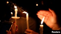 People attend a candlelight vigil for victims of yesterday's shooting at nearby Marjory Stoneman Douglas High School, in Parkland, Florida, U.S. Feb. 15, 2018.