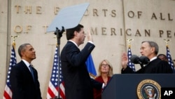 President Barack Obama watches as FBI Director James Comey takes an oath as FBI director from Judge John Walker, right, as Comey's wife Patrice Failor watches at center, during Comey's installation ceremony at FBI Headquarters in Washington, Oct. 28, 2013