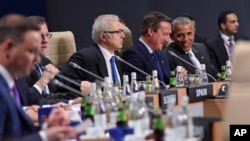 U.S. President Barack Obama, seated right, talks with British Prime Minister David Cameron, 2nd right, before the start of a session of the North Atlantic Council at PGE National Stadium in Warsaw, Poland, Saturday, July 9, 2016.