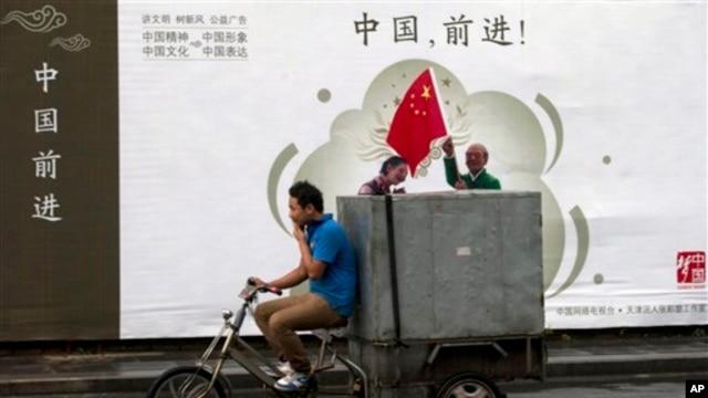 """2013年7月15日北京送货自行车驶过宣传广告牌""""中国,前进!"""""""