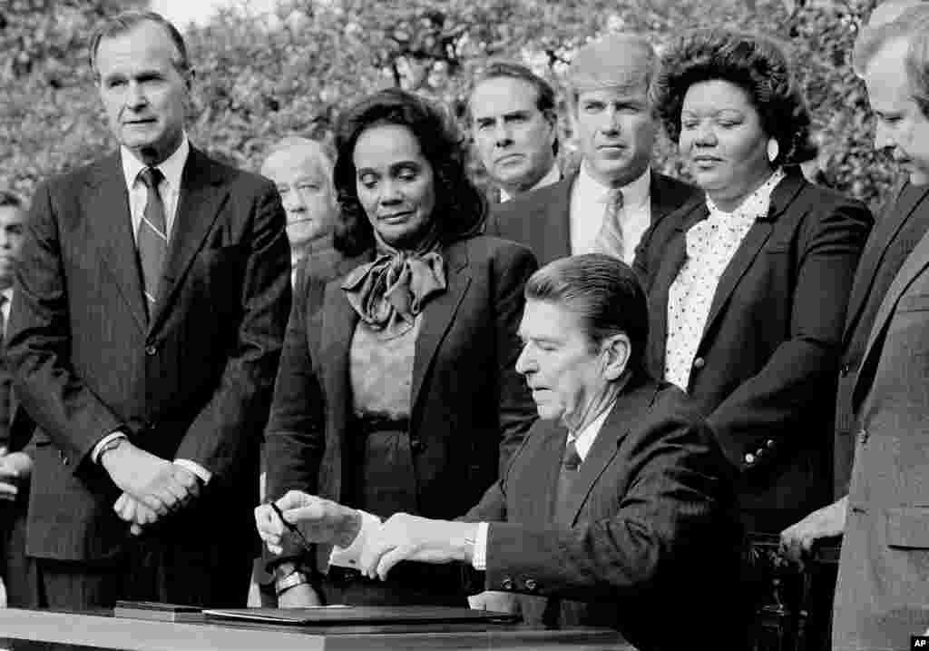 امروز در تاریخ: سال ۱۹۸۳- رونالد ریگان چهلمین رئیس جمهور آمریکا، لایحهای که تولد مارتین لوتر کینگ جونیور را تبدیل به تعطیلی رسمی میکرد، امضا کرد. کورتا اسکات کینگ همسر مارتین لوتر کینگ پشت سر ریگن ایستاده است. /ت
