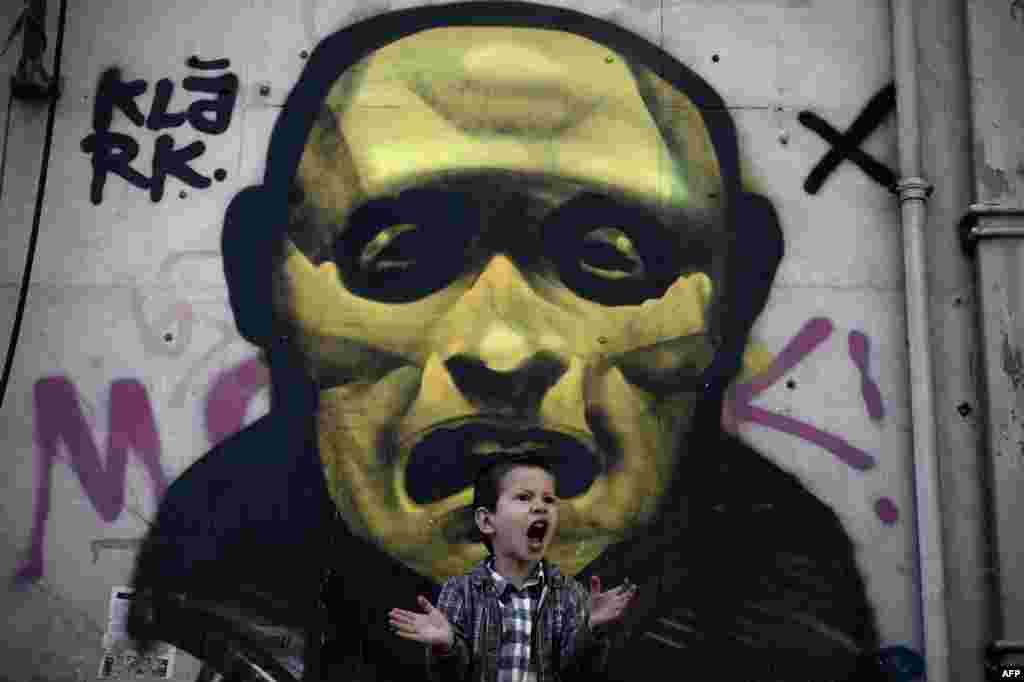 Cậu bé la hét trước bức tranh vẽ trên tường ngoài đường phố ở trung tâm Athens trong một buổi lễ đánh dấu ngày quốc khánh Hy Lạp.