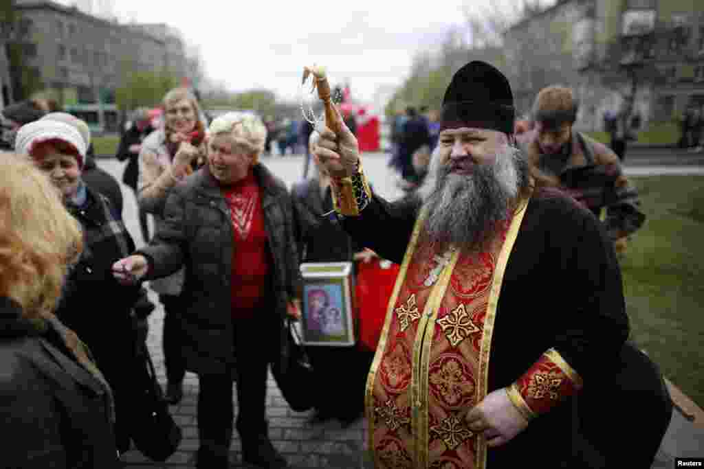 A Ukrainian Orthodox priest sprinkles holy water on believers outside a regional government building during Easter in Donetsk, eastern Ukraine, April 20, 2014.