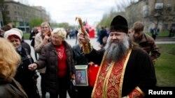 یک کشیش ارتدوکس اوکراینی در برابر یک ساختمان دولتی به روی مؤمیان آب مقدس می پاشد - دونتسک، ۱۹ آوریل