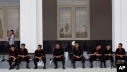 Sniffer dogs and members of Burma's bomb squad rest after checking Myanmar International Convention Center, the venue for the 24th ASEAN Summit for explosives in Naypyitaw, Burma, May 9, 2014.