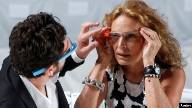 FILE - Google founder Sergey Brin (L) adjusts a pair of Project Glass glasses on designer Diane von Furstenberg before the rehearsal for von Furstenberg's Spring/Summer 2013 collection show during New York Fashion Week.