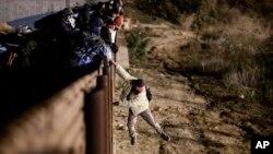 Seorang migran melompat dari pagar perbatasan AS-Meksiko untuk masuk ke wilayah AS di dekat Tijuana, Meksiko, 1 Januari 2019 lalu.