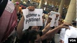 "Warga Israel yang juga aktivis pro-Palestina membawa poster ""Selamat Datang ke Palestina"" untuk menyambut para aktivis dari Eropa di bandara Ben Gurion dekat Tel Aviv, Jumat (8/7)."