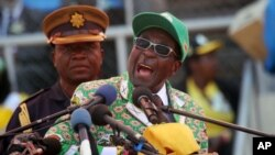 FILE: Zimbabwe President and Zanu-PF leader Robert Mugabe addresses party supporters at his last campaign rally in Harare, July, 28, 2013.