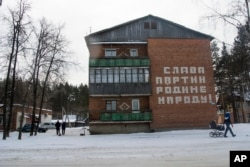 """People walk past a house with a Soviet-era slogan that reads """"Glory to the Party, Motherland and People!"""" in the village of Kedrovoye, Russia, Feb. 15, 2018."""