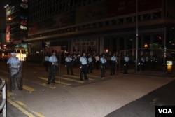 2019年7月7日午夜,九龙大游行的部分抗议者在旺角和警察对峙,警方封锁了商业街弥敦道旺角段 (美国之音记者申华拍摄)