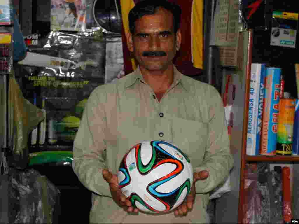 دکاندار برازیل فٹبال 2014 میں پاکستان کی تیارکردہ اوریجنل فٹ بال کی کاپی دکھارہاہے