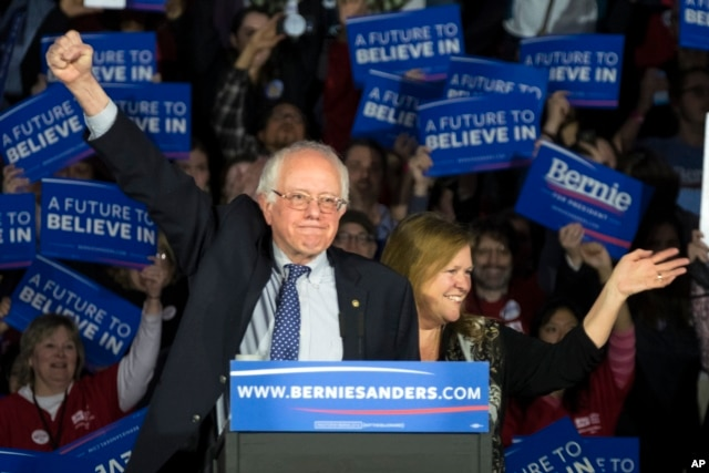 Democratic presidential candidate Senator Bernie Sanders of Vermont and his wave, Jane, acknowledge the crowd as he arrives for his caucus night rally in Des Moines, Iowa, Feb. 1, 2016.