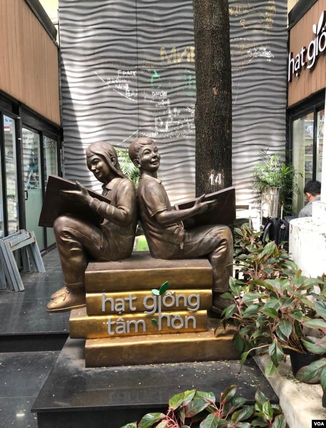 """Mấy tụ điểm để du khách chụp hình; trái, bức tượng đồng """"hai bé ngồi chống lưng đọc sách"""", phải, cô gái ngồi đàn guitare live trong một khu đọc sách ngoài trời. [photo by Ngô Thế Vinh]"""