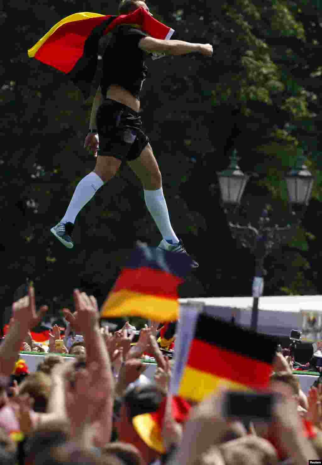 Penjaga gawang Jerman Manuel Neuer melompat ketika merayakan kemenangan timnya di Piala Dunia Brazil 2014, di tempat nobar Fan Mile di Berlin, 15 Juli 2014.