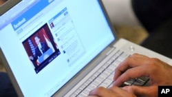 FILE - An Internet user in Los Angeles monitors a Facebook discussion board while watching televised coverage of President Barack Obama's speech from Cairo University, June 4, 2009.