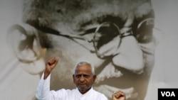 Anna Hazare mengacungkan kepalan tangan kepada para pendukungnya dengan latar belakangan gambar Mahatma Gandhi di New Delhi (19/8). Hazare memulai mogok makan 15 hari untuk mendesak penerapan UU anti-korupsi yang lebih tegas.