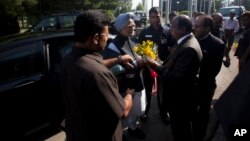 India's Prime Minister Manmohan Singh, center, is greeted by Chief Postmaster General John Samuel, right presenting a bouquet, in Srinagar, June 25, 2013.