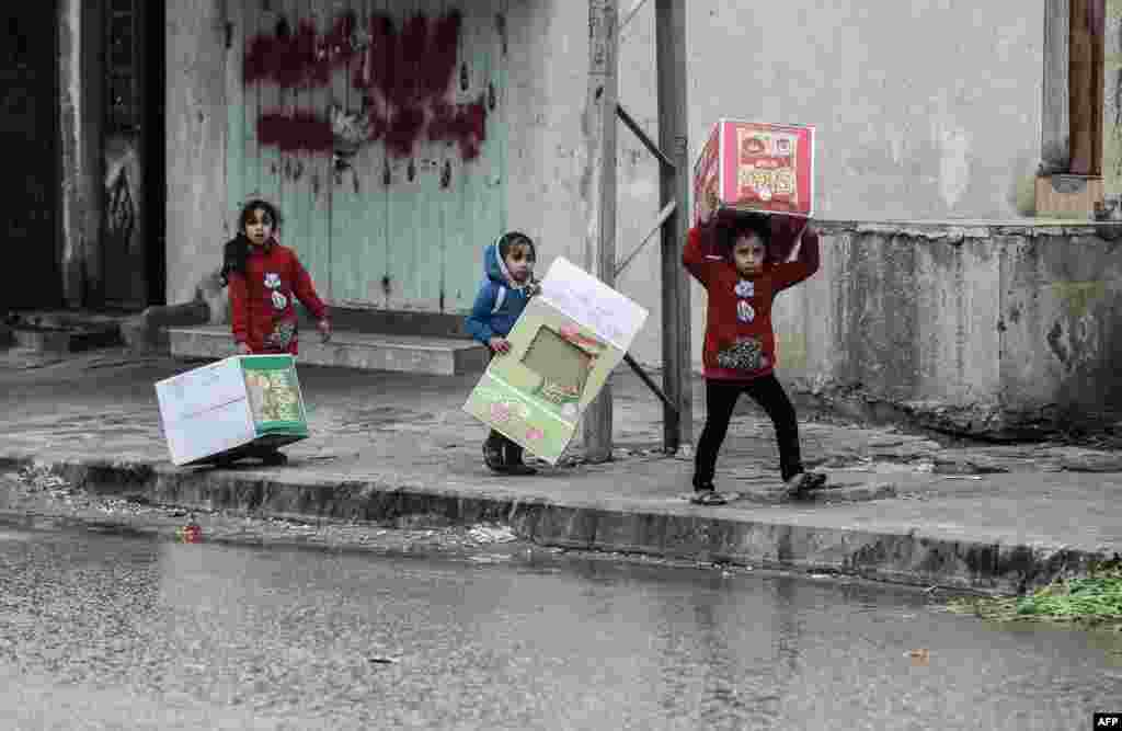 Palestinian girls carry cardboard boxes to shield themselves from the rain, in Rafah, in the Gaza Strip.