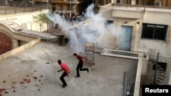 科普特基督徒在星期日與穆斯林的衝突中在警察施放催淚彈後再一座建築屋頂逃跑。