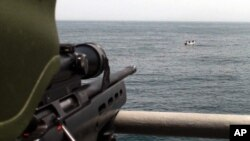 FILE - A Turkish commando, left, points his rifle toward five pirates surrounded in the Gulf of Aden, off the coast of Somalia, July 24, 2009.