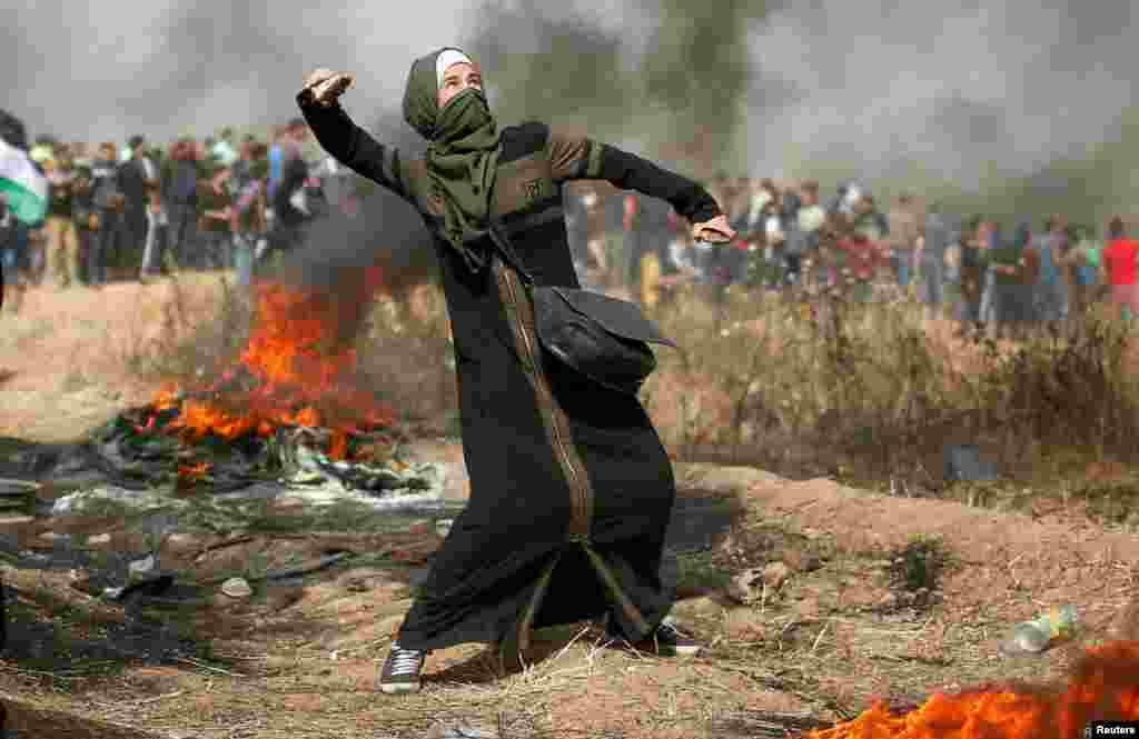 A girl hurls stones during clashes with Israeli troops at a protest where Palestinians demand the right to return to their homeland at the Israel-Gaza border, east of Gaza City.