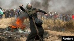 팔레스타인 여성이 최근 가자지구 시위에서 이스라엘 병력을 향해 돌을 던지고 있다
