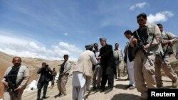 Presiden Afghanistan Hamid Karzai (tengah) menyalami warga desa korban tanah longsor yang mengungsi, saat mengunjungi mereka di distrik Argo, provinsi Badakhshan (7/5).