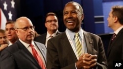 FILE - Dr. Ben Carson, center, waits for the the third debate between Democratic presidential nominee Hillary Clinton and Republican presidential nominee Donald Trump during the third presidential at UNLV in Las Vegas