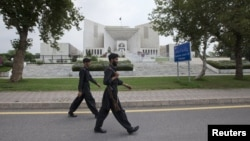 Paramilitary soldiers walk past the Supreme Court building in Islamabad, August 8, 2012.