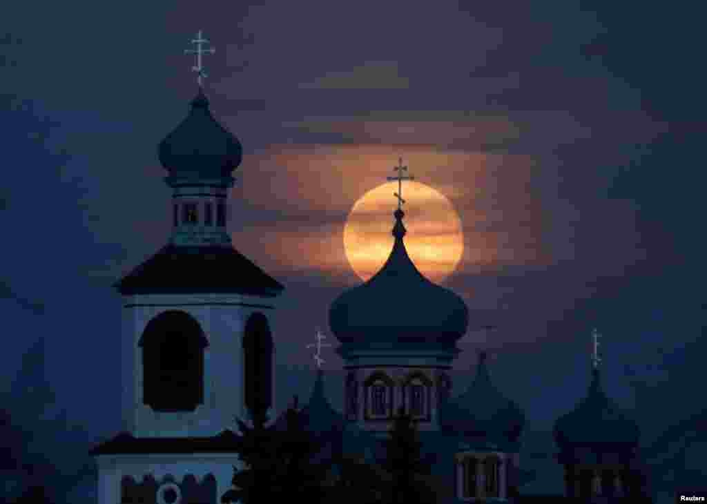 Full moon rises behind an Orthodox Church in the village of Turets, Belarus, Feb. 9, 2020.
