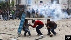 埃及抗议者11月20日在开罗解放广场附近躲避警察发射的催泪瓦斯和投掷回来的石块