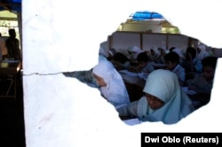 Siswa SMP terlihat melalui lubang di dinding saat mengikuti pembelajaran di gedung sekolah sementara di Bantul, Yogyakarta, 25 Mei 2007. (Foto: REUTERS/Dwi Oblo)