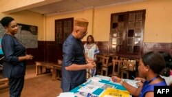 The Governor of the Central Region of Cameroon, Paul Naseri Bea's identity document is checked by electoral staff before proceeding to cast his vote in the general and municipal elections in Yaounde on Feb. 9, 2020.