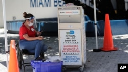 A poll worker wears personal protective equipment as she monitors a ballot drop box for mail-in ballots outside of a polling station during early voting, in Miami Beach, Florida. Aug. 7, 2020.