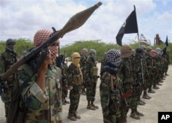 FILE - In this file photo of Thursday, Oct. 21, 2010, al-Shabaab fighters display weapons as they conduct military exercises in northern Mogadishu, Somalia. When Somalia's al-Qaida linked rebels withdrew from their bases in the capital last month, a host