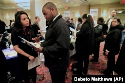 Daniela Silvero, left, an admissions officer at ASA College, discusses job opportunities with Patrick Rosarie, who is seeking a job in IT, during JobEXPO's 2012 job fair in New York.